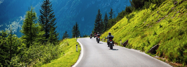 Vier motorrijders rijden door de bergen