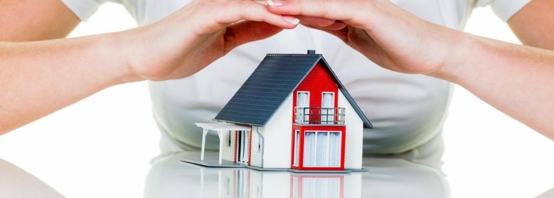 Vrouw met haar handen boven een huisje