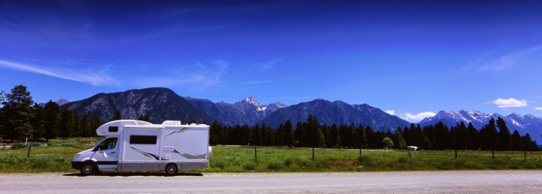 Camper rijd langs bergen op de weg