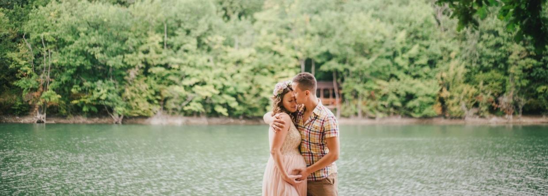 Zwangere vrouw staat met haar man bij een meer